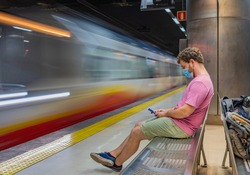 Mallorca public transport, Young man waiting for subway sitting on a bench alone with mask and safety distance due to covid-19 crisis using the phone while the subway passes in front of him