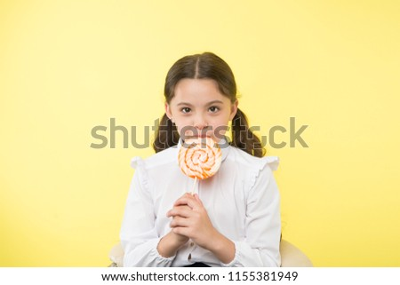 Malnutrition common problem. Girl pupil school uniform likes sweets lollipop candy yellow background. Girl cute kid ponytails hairstyle eat sweet lollipop. Sweets in appropriate portions ok.