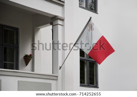 Malta flag. Maltese flag displaying on a pole in front of the house. National flag of Malta waving on a home hanging from a pole on a front door of a building.