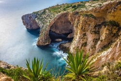 Malta - The famous arch of Blue Grotto cliffs with green leaves