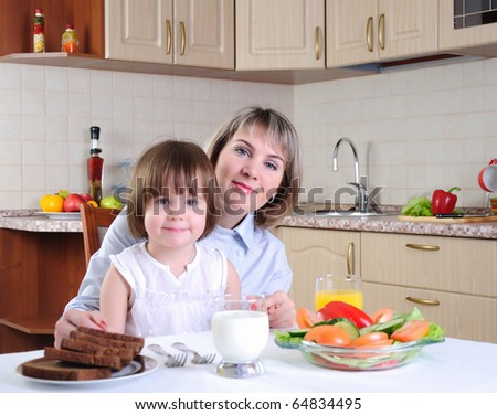 Mama and her little daughter eating breakfast in the morning together in the kitchen.