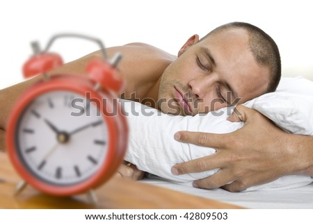 Man a sleep with big red alarm clock in the foreground. The focus is on the man.