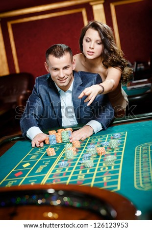 Man accompanied by woman placing bets at the casino table