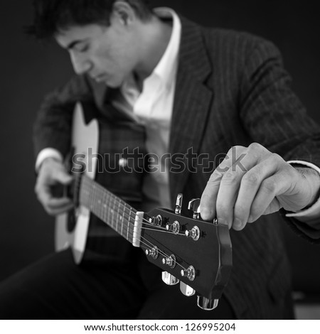 Man according guitar against black background. Black and white image. Shallow depth of field.