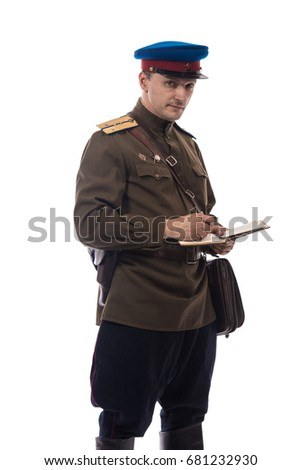 Man actor in the form of an officer captain People's Commissariat of Internal Affairs of Russia from the period 1943-1945 writes in a notebook and poses against a white background