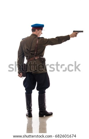 Man actor in the form of an officer captain People's Commissariat of Internal Affairs of Russia from the period 1943-1945 charges a gun and aims to shoot against a white background