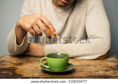 Man adding sugar to his coffee or tea #150050477