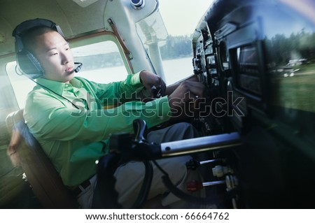 Man adjusting controls in airplane