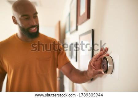 Man Adjusting Digital Central Heating Thermostat At Home Foto stock ©
