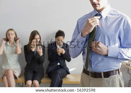 Man adjusting his tie, preparing for job interview, with fellow applicants in background