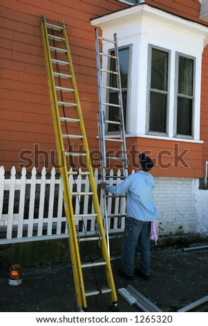 man adjusting ladder painting outside of house