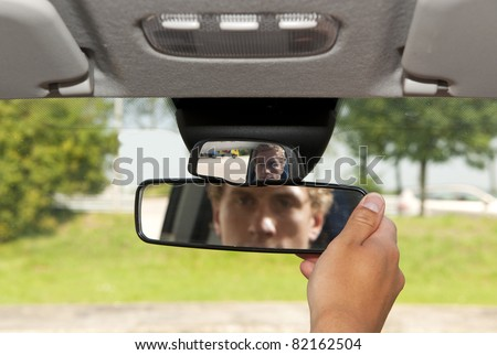 Man, adjusting the rear view mirror of his car