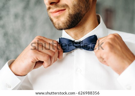 man adjusts his blue bowtie in a white shirt. attractive young man is standing in a room. closeup photo of bowtie
