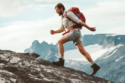Man adventurer skyrunning in mountains with backpack Norway Travel hiking lifestyle concept active weekend summer vacations athletic person