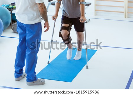 Man after car accident in an orthosis and on crutches learning to walk in the clinic, helpful therapist near him Stock photo ©