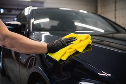 Man after washing wipes black car with a rag at car wash. Male hand and car body close up.