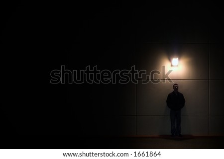 man against a wall and light by a single light