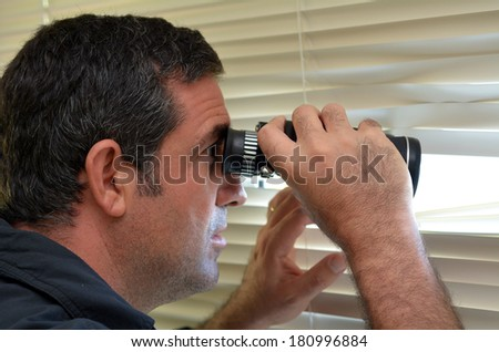 Man (age 35-40 ) looks and searches with binoculars and  looks out through Venetian blinds. Concept photo of curious, spy, nosy man.