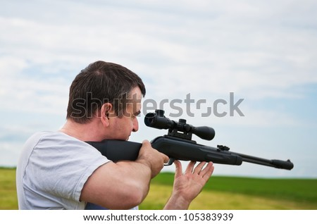 man aiming, looking into the scope of his rifle