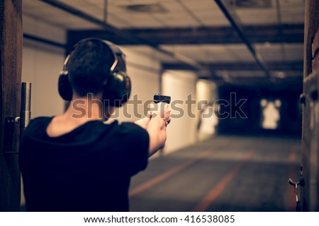 Man aiming pistol at target in indoor firing range or shooting range - Shutterstock ID 416538085