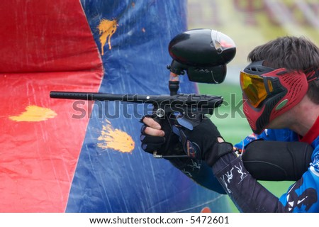 man aiming with paintball gun from cover