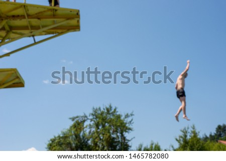 Man, airborne after jumping off a water jumps tower into pool, blurred