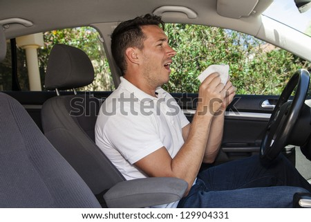 Man allergic to pollution or pollen sneezing inside a car.