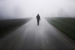 Man alone on foggy road