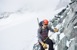 Man alpinist in sunglasses and safety helmet holding fixed rope while climbing snowy mountain. Mountaineer ascending natural rock formation. Concept of mountaineering and winter rock climbing.