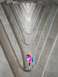 man amd son with his colourful umbrella on abstract pattern background of multiple concrete poles by using telephoto lens
