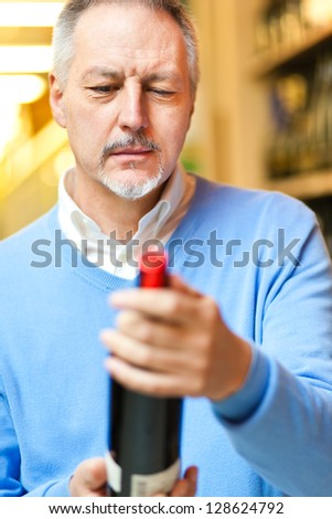 Man analyzing a bottle of red wine in a supermarket - stock photo