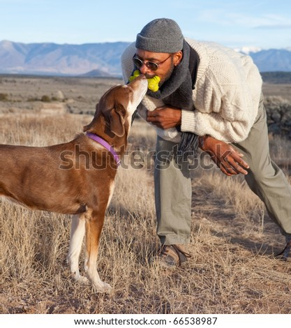 Man and a dog sharing a toy bone (ew!), playing.