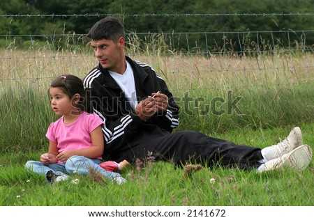 Man and a little girl sitting together on the grass looking at something in the distance with a wire fence and field to the rear. Man is holding a cigarette in his hand.