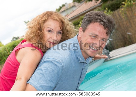 man and a senior woman for a piggyback in front of the pool #585083545