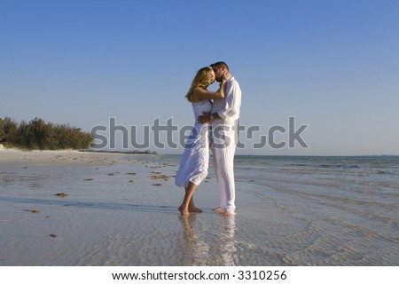 Man and a woman kissing on a beach.  Both wearing white clothes.