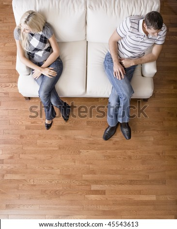 Man and a woman sit distantly on the ends of a cream colored love seat. Their heads are turned away from each other. Vertical shot.