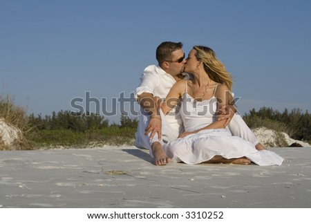 Man and a woman sitting on a beach, kissing.  Both wearing white clothes.