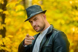 Man and autumn. A man on a yellow autumn background. A brutal man with a beard, a black leather jacket and a hat shows a finger gesture forward on an autumn yellow background.