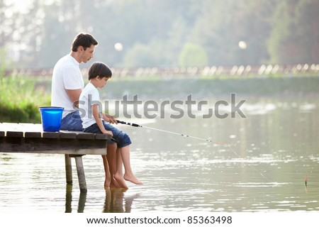 Man and boy fishing on the lake - stock photo