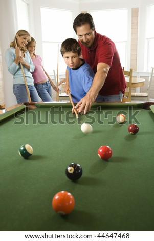 Man and boy playing pool with woman and girl in background. Vertically framed shot.