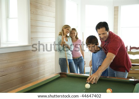 Man and boy shooting pool with woman and girl in background. Horizontally framed shot.