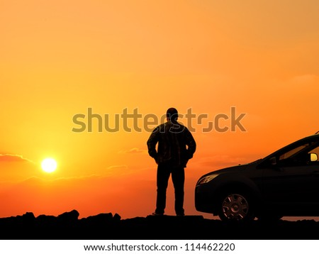 Man and car silhouettes against orange sunset