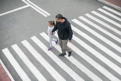 Man and child on a zebra crossing trespassing by crossing the street. In the summer on the street kid girl with her father in fashion clothes cross the road. From top view. Traffic rules for children