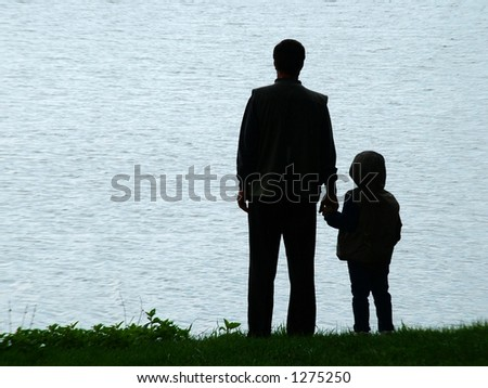 Man and child silhouette at lakeside in evening