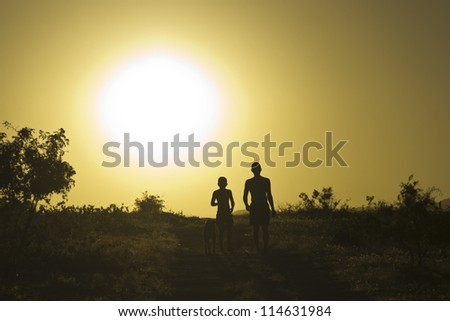 Man and child walking the dog at sunset