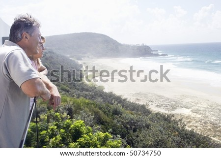 Man and Daughter Looking out at Ocean from balcony of vacation house, side view