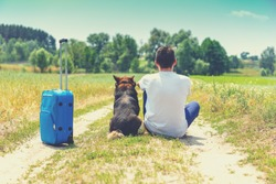 Man and dog are best friends and travelers. Man and the dog sit together with travel suitcase back to camera on dirt road in the field in summer. Wanderlust