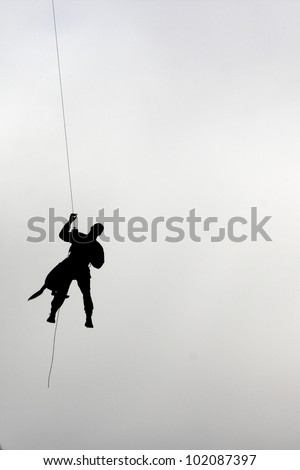 man and dog climbing down from a helicopter