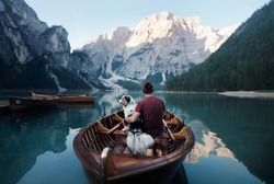 man and dog in a boat on a mountain lake. Traveling with a pet to Italy. Australian Shepherd Dog and its owner