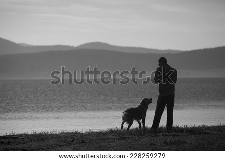 man and dog near high mountain lake in sunset time, black and white landscape